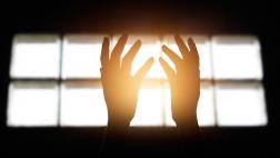 Zum Himmel gestreckte Hände in einem dunklen Raum.