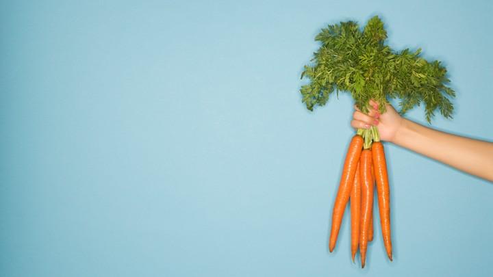 Eine Hand mit einem Bund frischer Karotten.