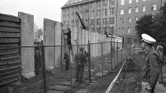 """Ein Bautrupp verspachtelt die neu errichteten Betonsegmente, während ein Kran die Rohrauflage auf die neue """"Grenzmauer 75"""" setzt."""